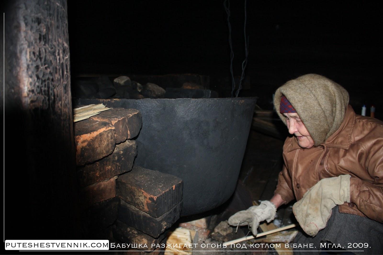 Русская бабушка подкладывает дрова под котел в бане
