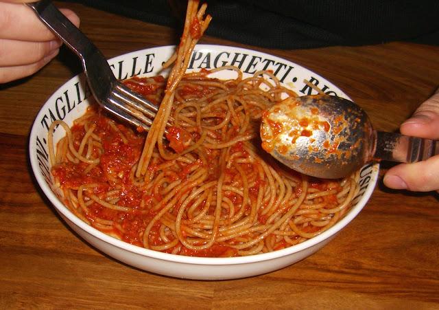 Foto van iemand die een bord spaghetti puttanesca eet