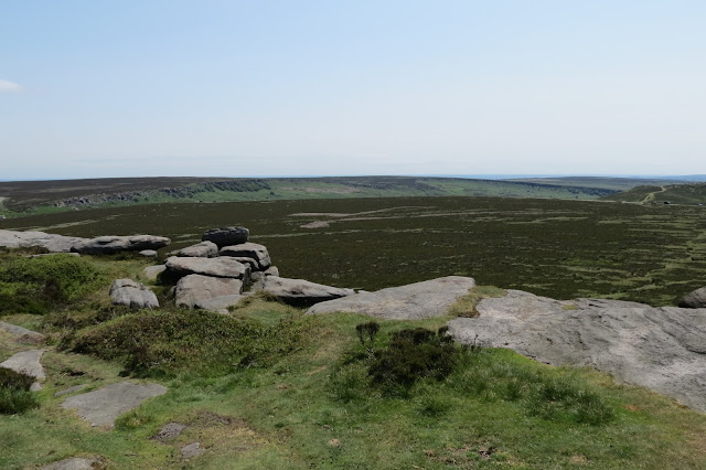 A view across open moorland to Burbage Rocks, a crescent-shaped escarpment with a gap in the middle.