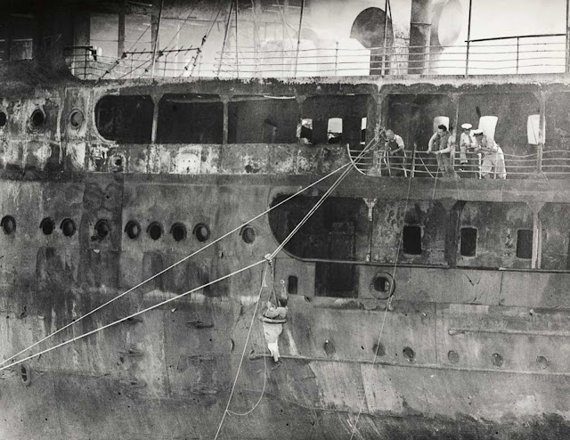 Men climb aboard the wreck to search for bodies.
