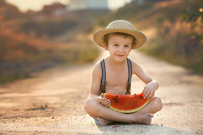 boy-eating-Watermelons-sitting-on-the-ruff-road