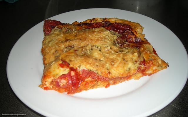 Foto van een stuk zelfgemaakte pizza op een wit bord