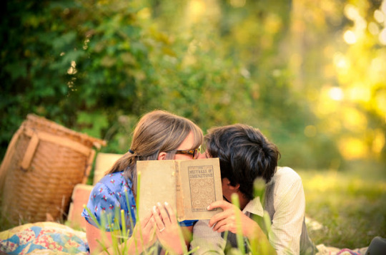 Engagement photo of a couple on a picnic, kissing behind a book