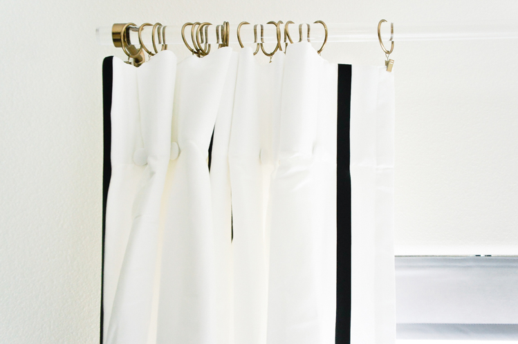 Lucite drapery rod, white curtain panels hung with warm gold curtain clips in a master bedroom.