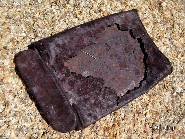 The remains of an old tobacco tin, found near other rusted cans at the miner's camp.
