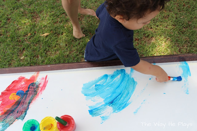 Toddler painting with a paint brush