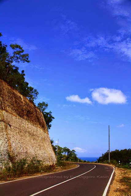 Foto Jalan membelah bukit kapur di sepanjang pantai