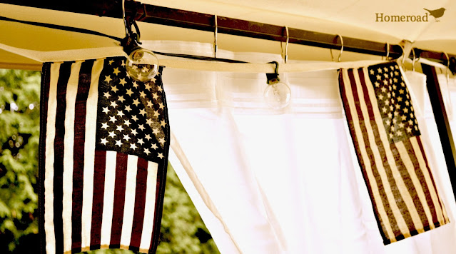 American flags hanging with lights in an outdoor gazebo