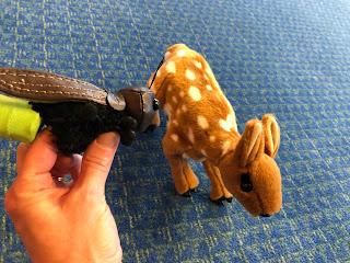 hand holding firefly puppet next to a deer puppet