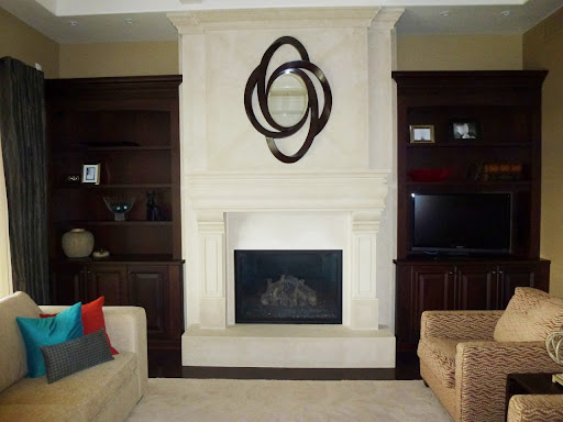 close up of COCOZY reader's great room with almost empty built in bookshelf, fireplace with molded mantel, neutral sofa with three accent pillows one blue, red and patterned and two arm chairs