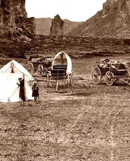 A sepia photograph of a small canvas tent, two small wagons, and curricle. In the background is the entrance to a mountain pass with a small outcropping in the middle like a large pillar. A man wearing a wide-brimmed black hat looks out of the tent opening, and a girl in a bonnet stands in front.