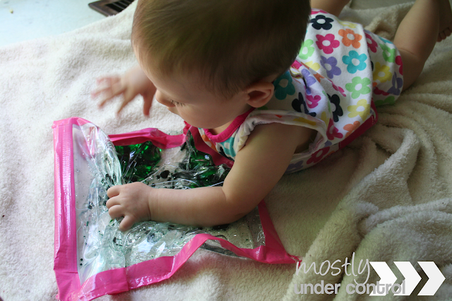 Baby on her stomach playing with a sensory water bag