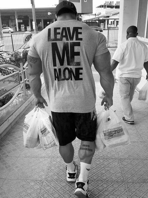 Huge bodybuilder wearing a light grey 'LEAVE ME ALONE' T-Shirt