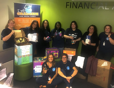 Group photo of financial aid team next to donation boxes