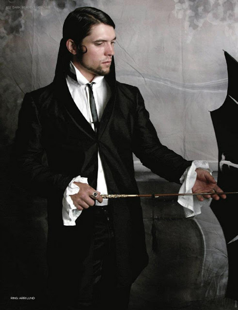 Man in steampunk clothing. Black jacket, trousers, white ruffle shirt with black tie. His hair is slicked back and he carries a black umbrella. For gothic victorian fashion, steamgoth cosplay, halloween costume or neo-victorian steampunk clothes.