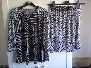 Blusa e saia em tecido fluíd e diferentes padrões em tons de cinza, branco e preto.