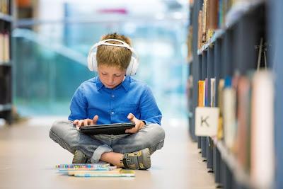 Berniukas skaito garsinę knygą su ausinėmis, rankose skaityklė, jis sėdi bibliotekoje ant grindų