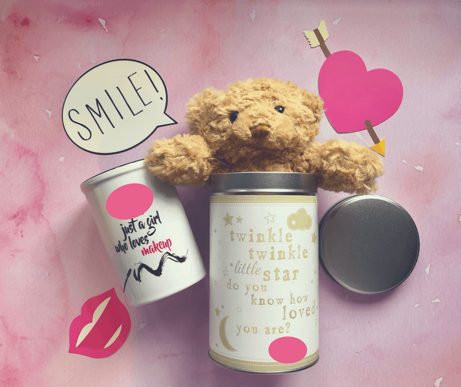 "A teddy bear sticks out of the top of a tin with the words ""twinkle twinkle little star, do you know how loved you are"" written in gold on the front. Next to the tin is a ceramic make up brush holder with the words ""just a girl who loves make up"" on the front in black. There's a pink marble effect background."