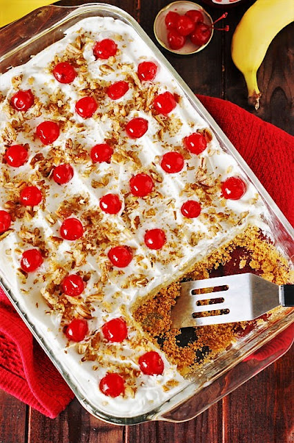 No-Bake Banana Split Cake Topped with Maraschino Cherries Image