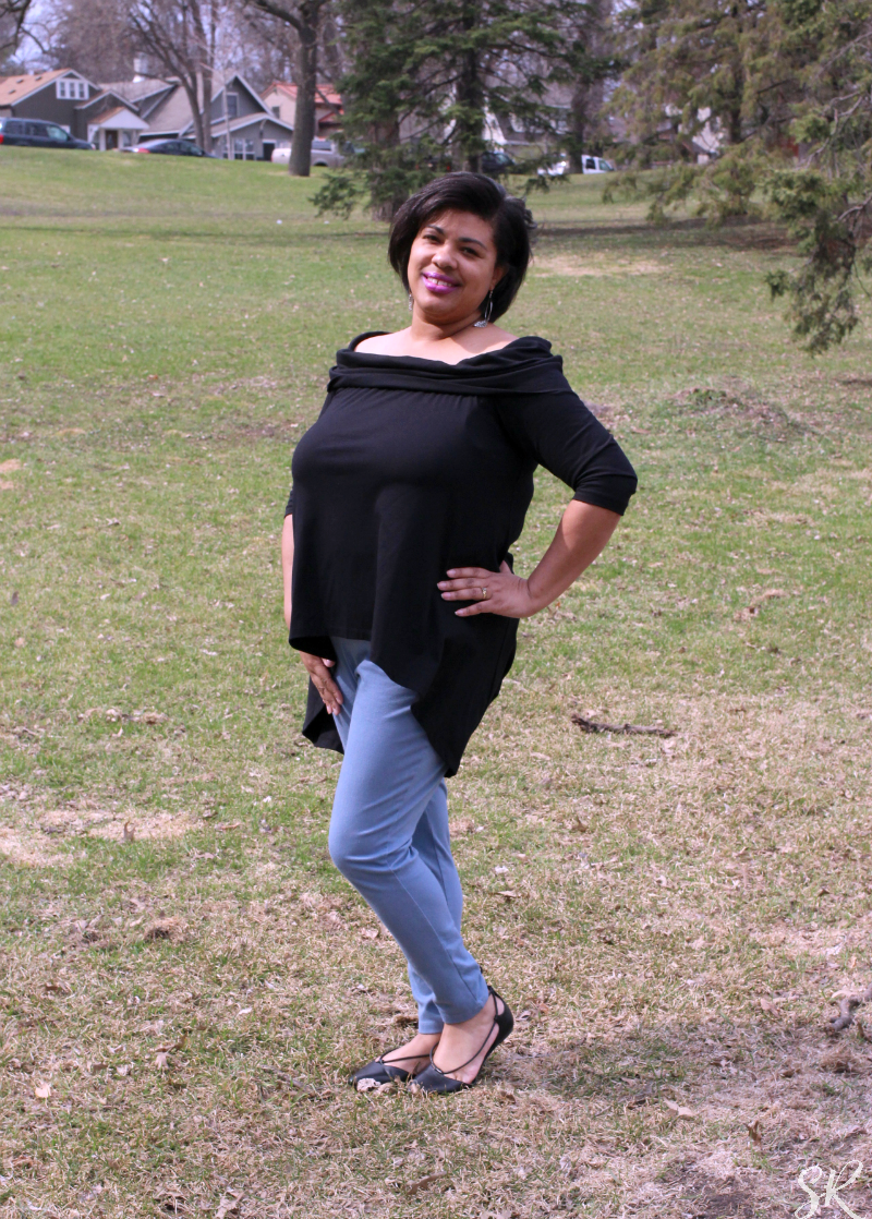 a woman posing in a black off the shoulder shirt
