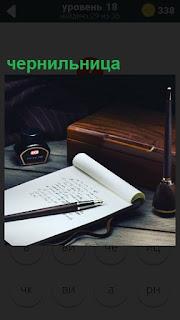 Лежит блокнот и ручка для записей, рядом бутылочка чернильница