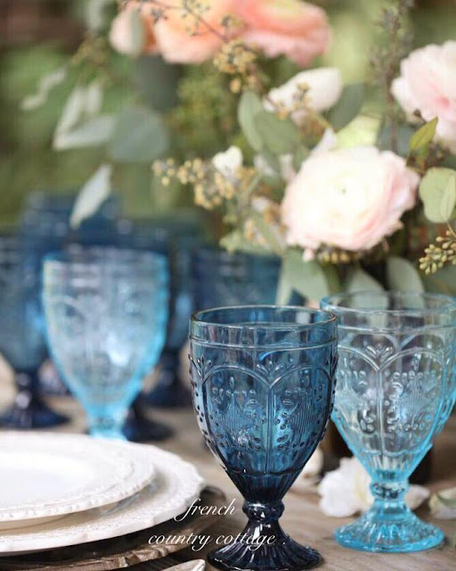Blue goblets with flowers on table