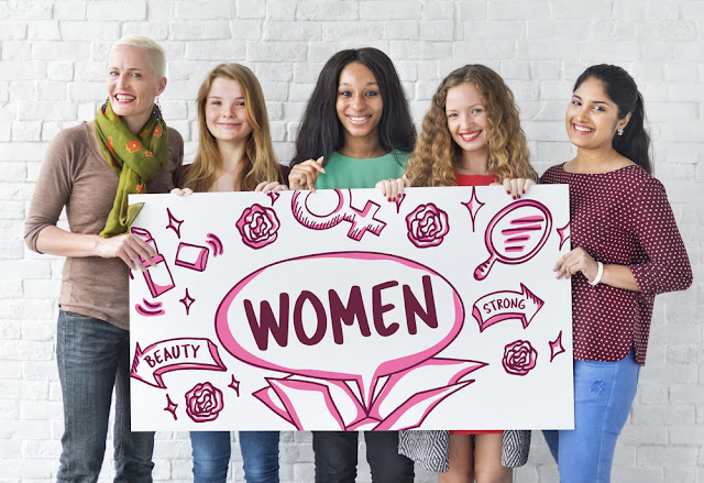 Different types of women holding a women's sign for equality