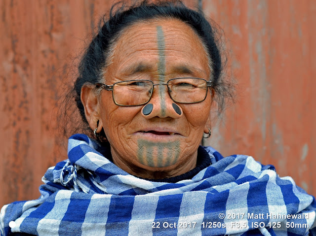 matt hahnewald photography; facing the world; character; face; tattoo; face tattoo; tribal tattoo; eyes; eyeglasses; nose; nose plugs; lived-in face; wrinkles; facial expression; eye contact; consent; empathy; respect; rapport; ethnic; traveling; tribal; adivasi; rural; village; traditional; cultural; hong; ziro; arunachal pradesh; northeast india; asian; indian; apatani; one person; female; adult; old; woman; picture; photo; illustrative editorial; face perception; physiognomy; educational; nikon d3100; nikkor af-s 50mm f/1.8g; prime lens; 50mm lens; nifty fifty; 4x3 aspect ratio; horizontal orientation; street; portrait; closeup; headshot; seven-eighths view; blue; outdoors; color; posing; authentic; unique; yaping hullo; yesso; shutterstock