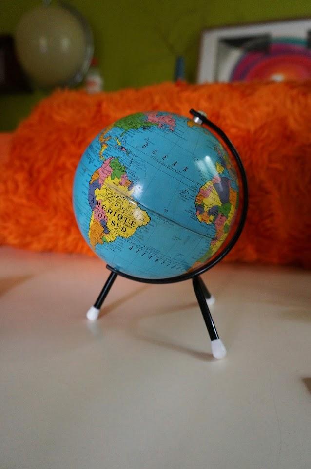 un mini globe tripode des années 60 et en fond, un couvre lit orange des années 70  60s tripod globe , 70s orange faux fur bedspread
