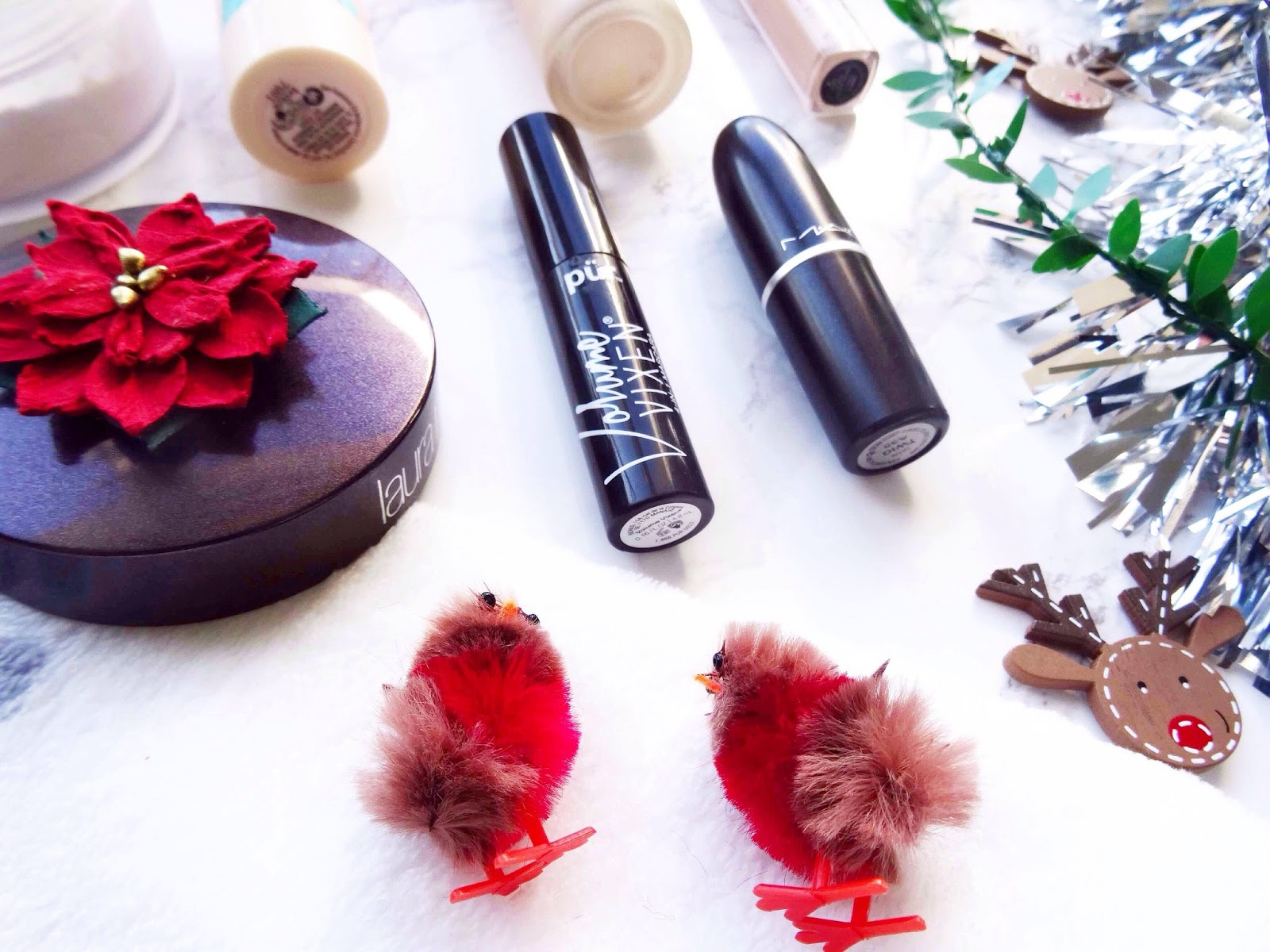 Two Christmas Robins infront of Makeup Products