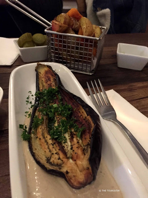 Roasted eggplant, garnished with parsley, served on a bed of hummus.