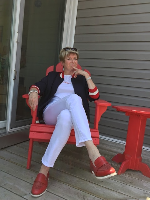 woman in white jeans and tee and a baseball jacket sitting in a red deck chair