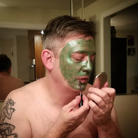 image of Deeky sitting in my dining room wearing a green face peel and applying the lipstain