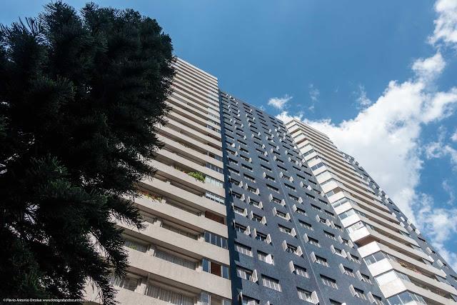 Olhando para cima - edifício com árvore em primeiro plano