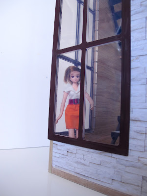 A doll looking through the corner window of the modern Lori Loft to Love dolls' house.