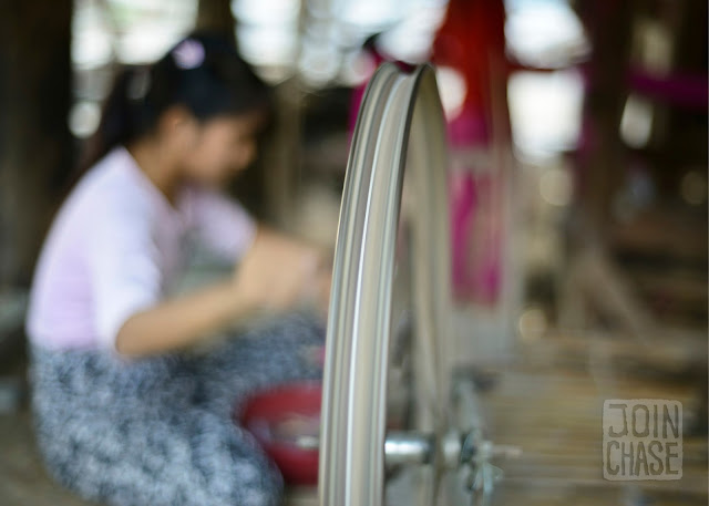 A woman spinning pink thread to prepare for weaving in Sagaing Division, Myanmar.