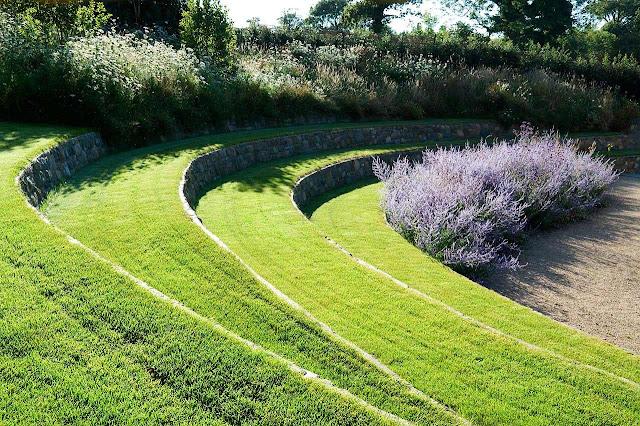 gradina teren in panta design gradina simpla zid de sprijin amfiteatru gazon natural design curte teren in panta peisagistica land art sculptura pamant piatra naturala stabiliare pamant