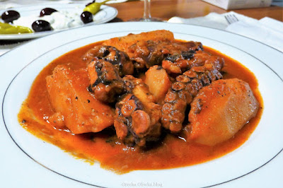 Na talerzu: ośmiornica w sosie pomidorowym z ziemniakami obok talerz z tzatzyki i oliwkami
