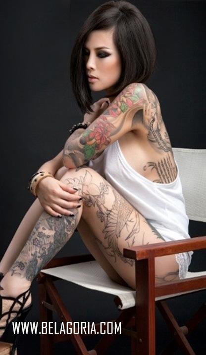 vemos a una mujer asiatica sentada, nos deja ver en sus costillas un tatuaje tailandes