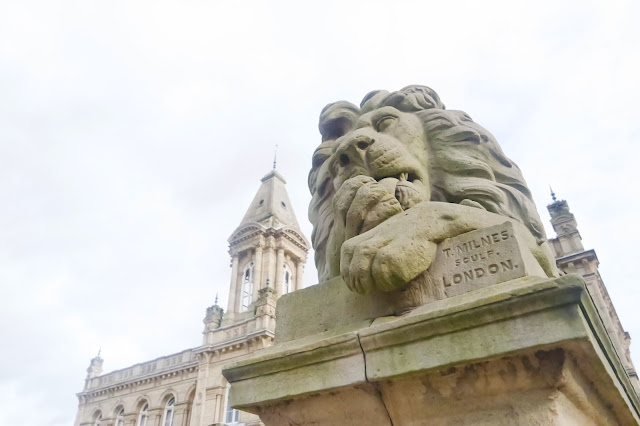 a stone lion statue stands in front of victora hall, a large stone building