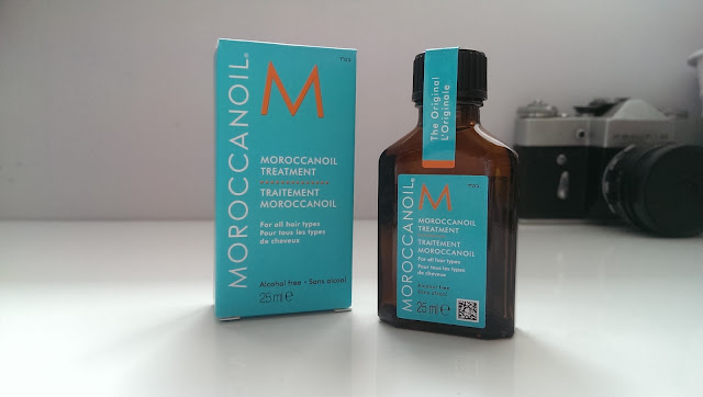 A bottle of Moroccanoil treatment next to its box