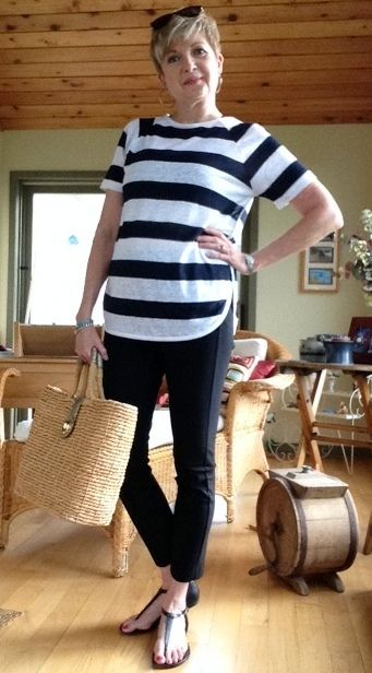 Woman in striped tee, black pants and holding a straw tote