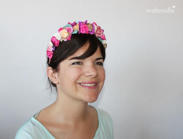 Chica de frente de pelo moreno con look de diadema flores en varios colores, predomina el fucsia