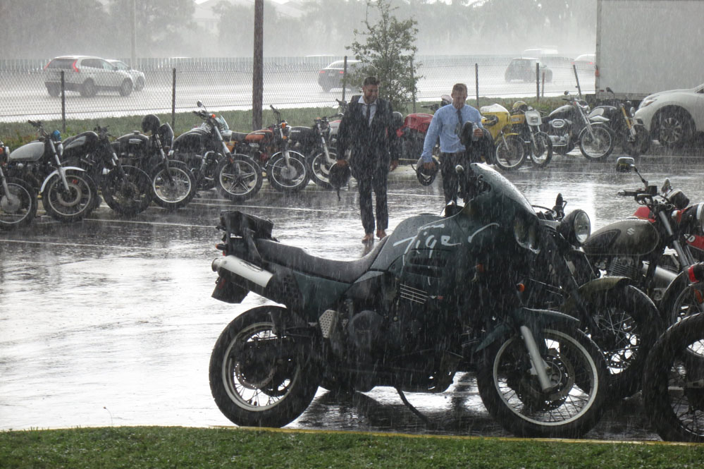 Motorcycles parked in the rain.