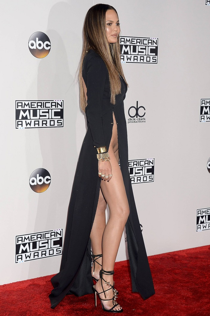 Chrissy Teigen suffers a wardrobe malfunction after wearing no underwear and a dress held together by pins at AMAs