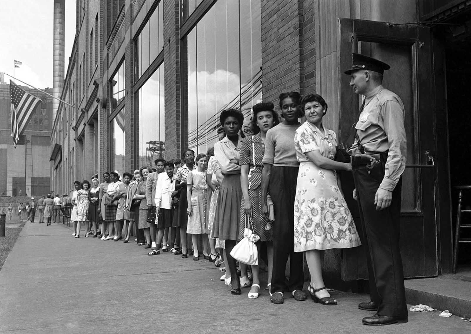 Men and women, formerly employed in defense work, crowd Detroit branch of War Manpower Commission to file claims for unemployment benefits and also register for new jobs on August 17, 1945.