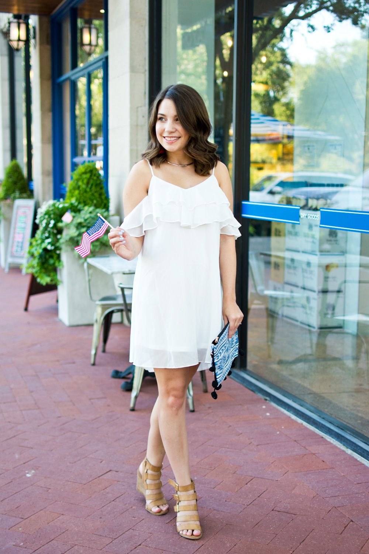 White cold shoulder dress with pom pom clutch