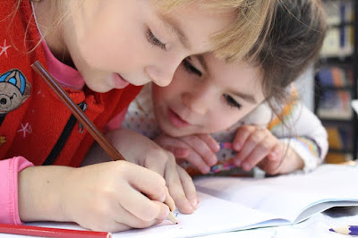 two children writing in a notebook