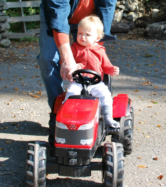 Child on red tractor with adult helping hand