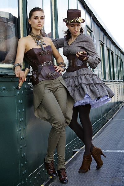 Two women wearing Steampunk clothing. One wears a corset with pants, the other wears a corset with dress.